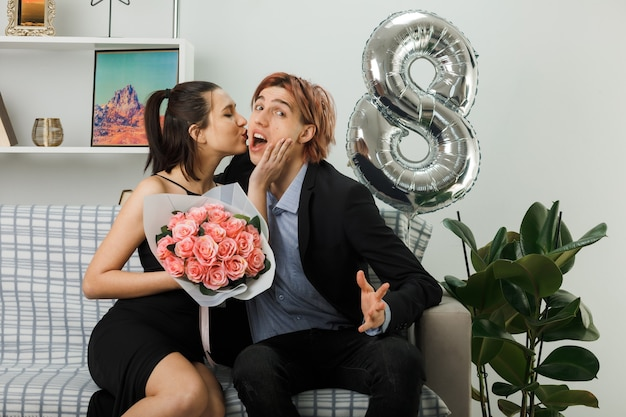 Blij jong koppel op gelukkige vrouwendag meisje met boeket kussende man zittend op de bank in de woonkamer