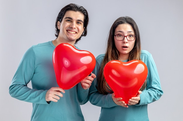 Blij jong koppel op valentijnsdag met hart ballonnen geïsoleerd op een witte achtergrond