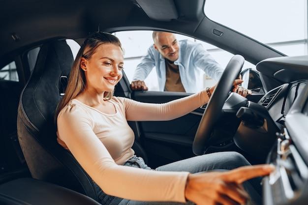Blij jong koppel rondkijken in een nieuwe auto die ze gaan kopen in een autowinkelbedrijf