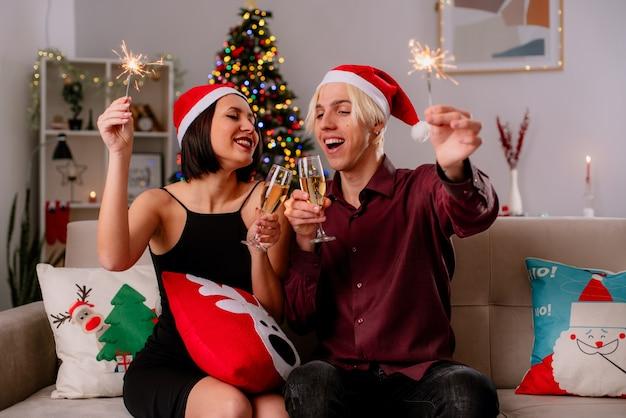 Blij jong koppel thuis in de kersttijd met kerstmuts zittend op de bank in de woonkamer