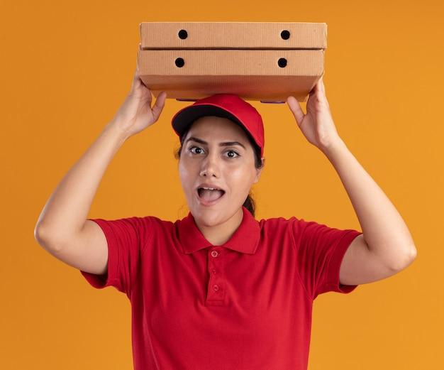 Blij jong leveringsmeisje die eenvormig en glb dragen die pizzadozen op hoofd houden die op oranje muur worden geïsoleerd