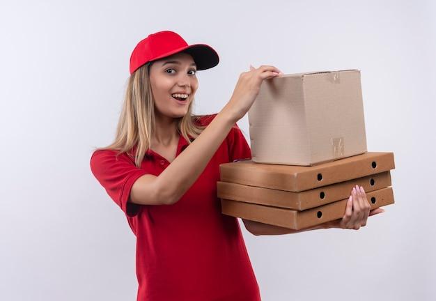 Blij jong leveringsmeisje die rood uniform en glb dragen die vele dozen houden die op witte muur worden geïsoleerd
