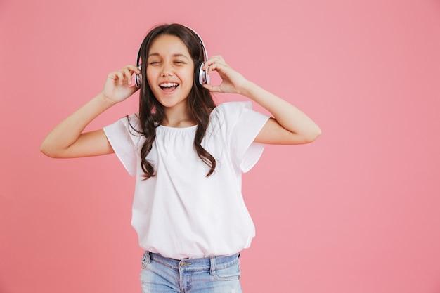 Blij jong meisje 8-10 in vrijetijdskleding zingen met gesloten ogen tijdens het luisteren naar muziek via draadloze koptelefoon, geïsoleerd op roze achtergrond