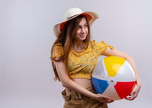 Blij jong meisje dat het strandbal van de hoedholding draagt ?? die naar rechterkant op geïsoleerde witte ruimte met exemplaarruimte kijkt