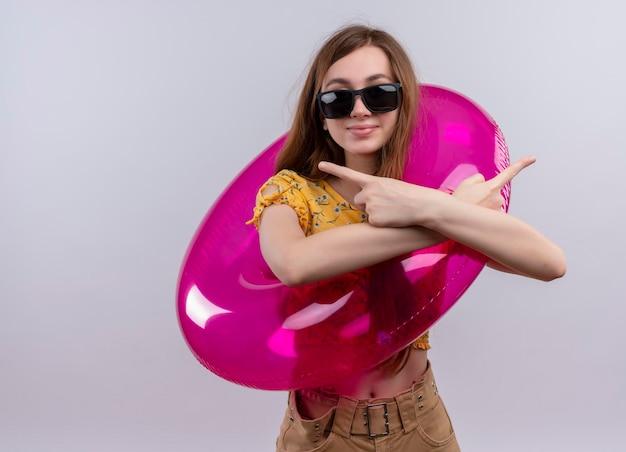 Blij jong meisje draagt een zonnebril en zwemt ring wijzend naar zijkanten op geïsoleerde witte ruimte met kopie ruimte
