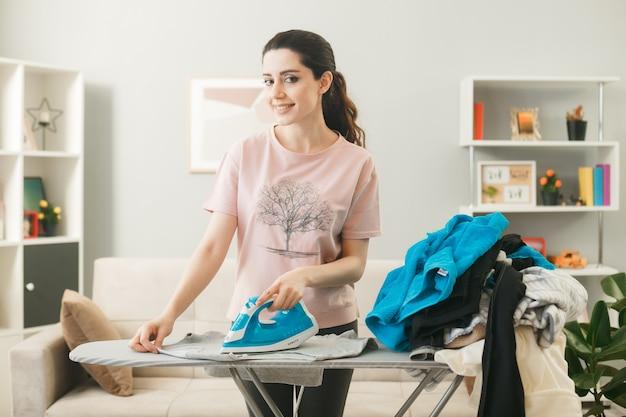 Blij jong meisje ijzeren kleren staan achter de strijkplank met kleren in de woonkamer