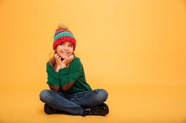 Blij jong meisje in sweater en hoed zittend op de vloer terwijl achterover leunt op haar wapens en weg kijkend over sinaasappel