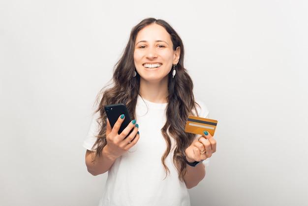 Blij jong meisje lacht naar de camera terwijl ze de telefoon en creditcard gebruikt die ze vasthoudt.
