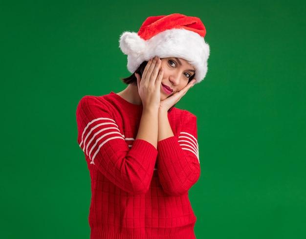 Blij jong meisje met een kerstmuts die de handen op het gezicht houdt en naar de camera kijkt die op een groene achtergrond met kopieerruimte wordt geïsoleerd