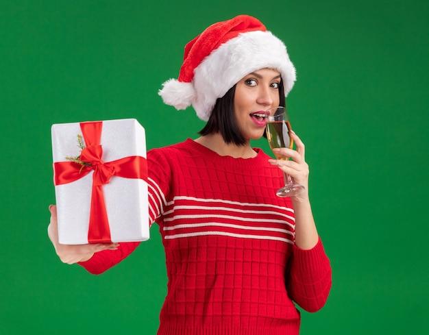 Blij jong meisje met een kerstmuts die een cadeaupakket naar de camera uitstrekt en een glas champagne drinkt die naar de camera kijkt die op een groene achtergrond wordt geïsoleerd
