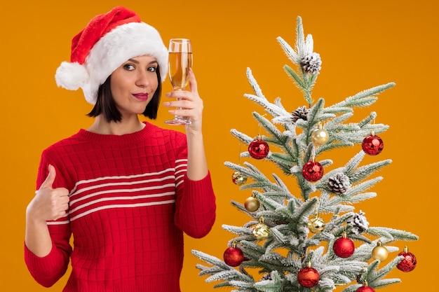 Blij jong meisje met kerstmuts staande in de buurt van versierde kerstboom met glas champagne kijken camera weergegeven: duim omhoog geïsoleerd op een oranje achtergrond
