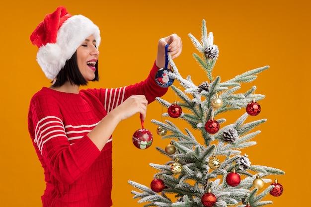 Blij jong meisje met kerstmuts staande in profiel te bekijken in de buurt van versierde kerstboom met kerstballen lachen met gesloten ogen geïsoleerd op oranje muur