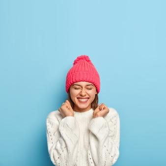 Blij jong meisje voelt zich dolgelukkig, steekt gebalde vuisten op, is in een goed humeur, draagt witte trui en roze hoed, gekleed in warme kleren tijdens koude herfstdag, geïsoleerd op blauwe muur