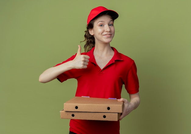 Blij jong mooi bezorgmeisje in rood uniform en pet met pizzapakketten en duim omhoog thumb