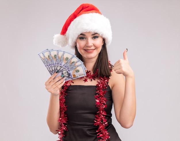 Blij jong mooi kaukasisch meisje met kerstmuts en klatergoudslinger om nek die geld aanhoudt kijkend naar camera die duim omhoog laat zien geïsoleerd op witte achtergrond