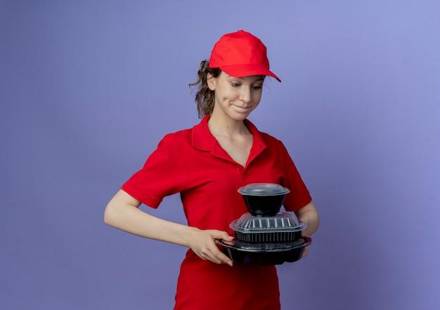 Blij jong mooi leveringsmeisje die rood uniform en glb dragen die en voedselcontainers bekijken die op purpere achtergrond met exemplaarruimte worden geïsoleerd
