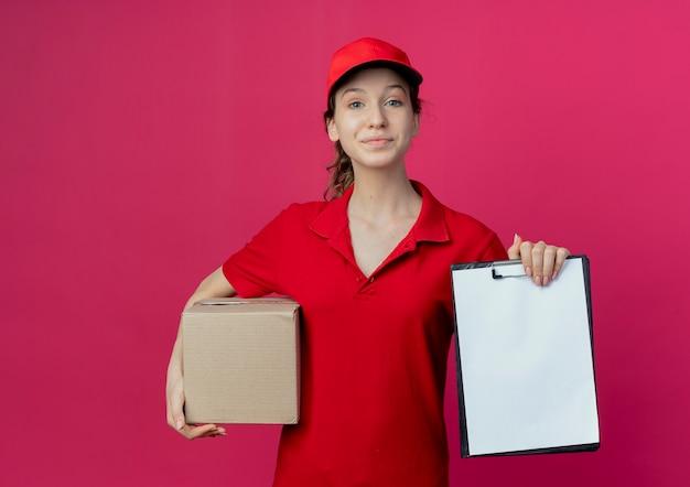 Blij jong mooi leveringsmeisje die rood uniform en glb dragen die kartondoos en klembord houden die op karmozijnrode achtergrond met exemplaarruimte wordt geïsoleerd