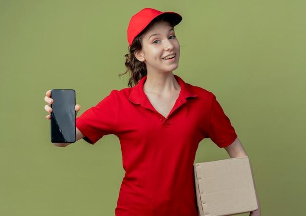 Blij jong mooi leveringsmeisje in rood uniform en glb die kartondoos houden en mobiele telefoon uitrekken bij camera die op olijfgroene achtergrond wordt geïsoleerd