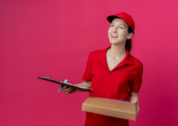 Blij jong mooi leveringsmeisje in rood uniform en glb-het pakketpen en het klembord die van de holdingspizza kijken die omhoog op karmozijnrode achtergrond wordt geïsoleerd