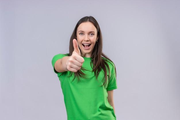 Blij jong mooi meisje dat een groene t-shirt draagt die vrolijk glimlachend duimen toont die zich over geïsoleerde witte achtergrond bevinden