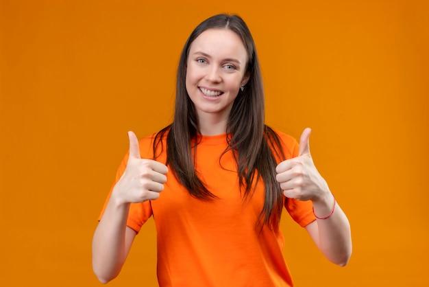 Blij jong mooi meisje dat een oranje t-shirt draagt die vrolijk glimlacht toont duimen met beide handen die zich over geïsoleerde oranje achtergrond bevinden