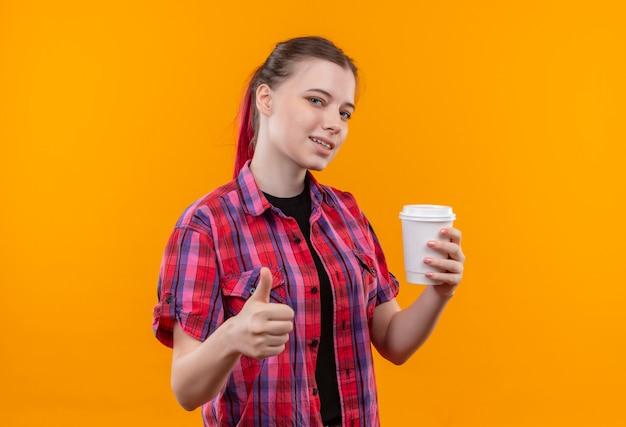 Blij jong mooi meisje dat een rode kop van de overhemdsholding van de koffie haar duim op geïsoleerde gele achtergrond met exemplaarruimte draagt