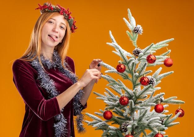 Blij jong mooi meisje dat in de buurt van een kerstboom staat met een rode jurk en een krans met een slinger op de nek die tong toont en een boom vasthoudt die op een oranje muur is geïsoleerd