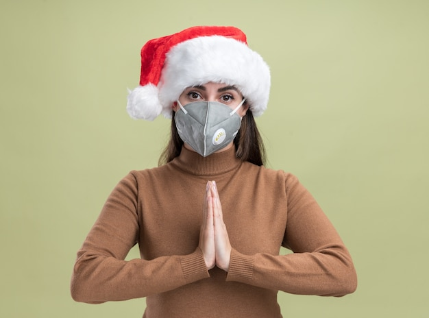 Blij jong mooi meisje dat kerstmishoed met medisch masker draagt dat bidgebaar toont dat op olijfgroene achtergrond wordt geïsoleerd