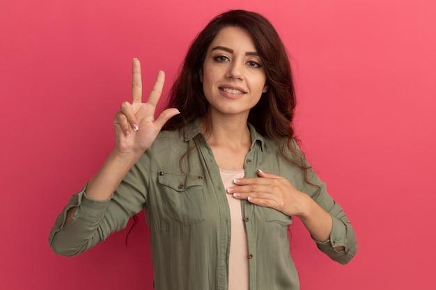 Blij jong mooi meisje dat olijfgroen t-shirt draagt dat vredesgebaar toont die hand op hart zetten dat op roze muur wordt geïsoleerd