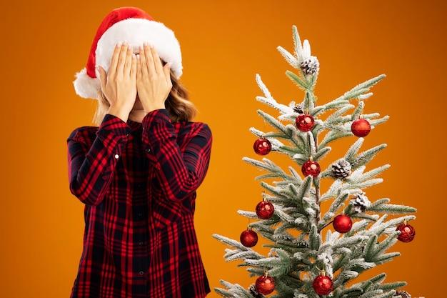 Blij jong mooi meisje dat zich dichtbij kerstboom bevindt die kerstmishoed bedekt die gezicht met handen draagt dat op oranje muur wordt geïsoleerd