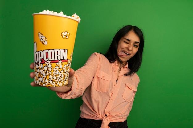 Blij jong mooi meisje die de roze emmer van de t-shirtholding popcorn dragen die tong tonen die op groen wordt geïsoleerd
