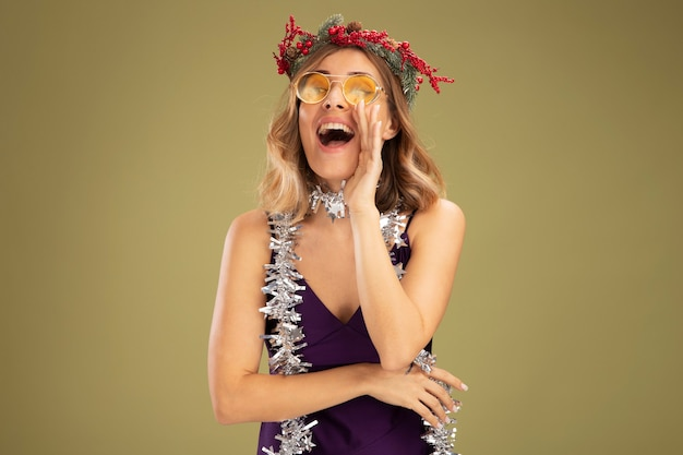 Blij jong mooi meisje die paarse jurk en glazen met krans en slinger op nek dragen die iemand bellen die op olijfgroene muur wordt geïsoleerd