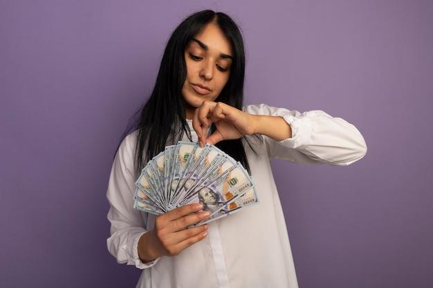 Blij jong mooi meisje die wit t-shirt dragen en geld bekijken dat op paars wordt geïsoleerd
