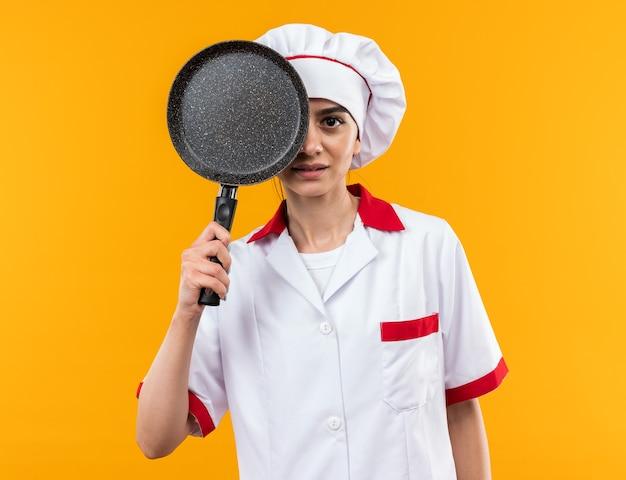 Blij jong mooi meisje in chef-kok uniform bedekt oog met koekenpan