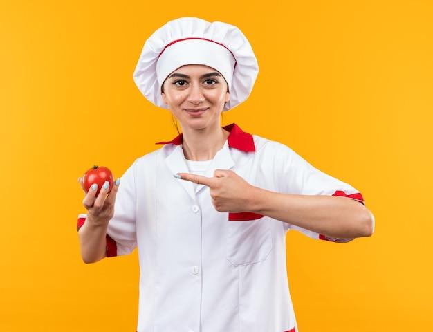 Blij jong mooi meisje in chef-kok uniform bedrijf en wijst naar tomaat geïsoleerd op oranje muur