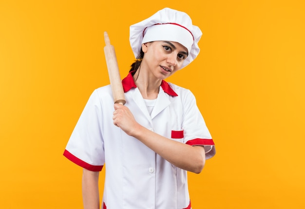 Blij jong mooi meisje in chef-kok uniform met deegroller op schouder geïsoleerd op oranje muur