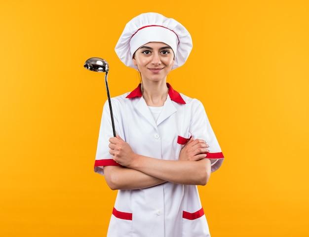 Blij jong mooi meisje in chef-kok uniform met pollepel die handen kruist geïsoleerd op oranje muur