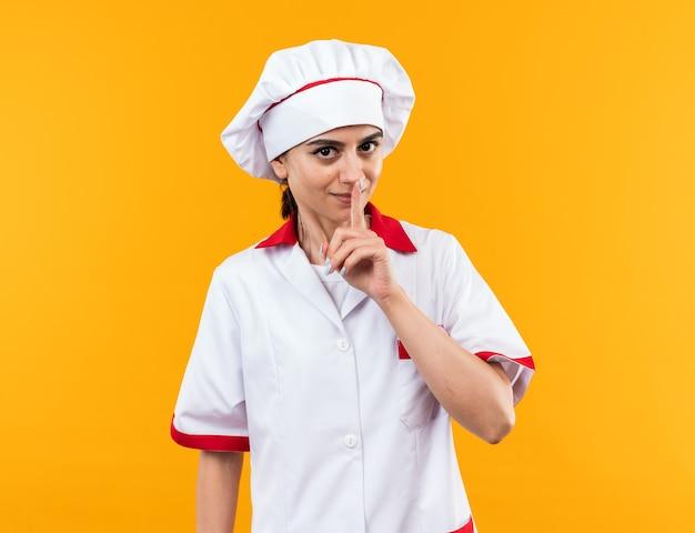 Blij jong mooi meisje in chef-kok uniform met stilte gebaar