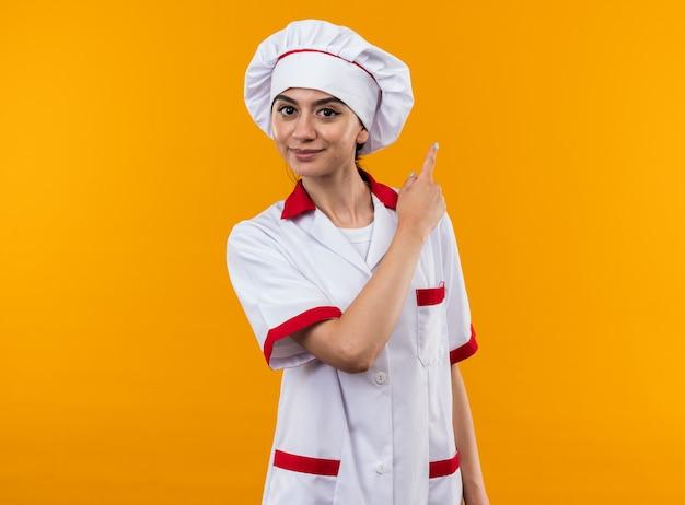 Blij jong mooi meisje in chef-kokuniform wijst naar achteren