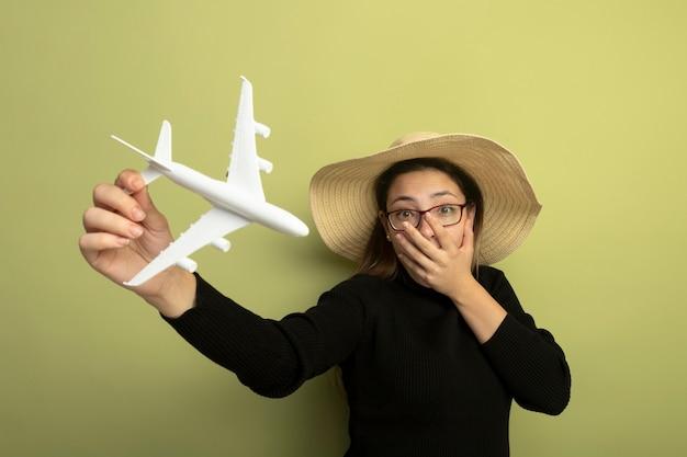 Blij jong mooi meisje in een zwarte coltrui en glazen die stuk speelgoed vliegtuig houden dat wordt geschokt die mond behandelen met hand