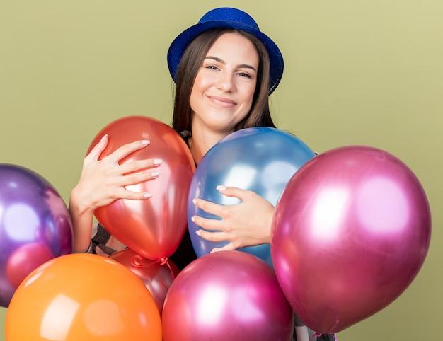Blij jong mooi meisje met blauwe hoed die achter ballonnen staat