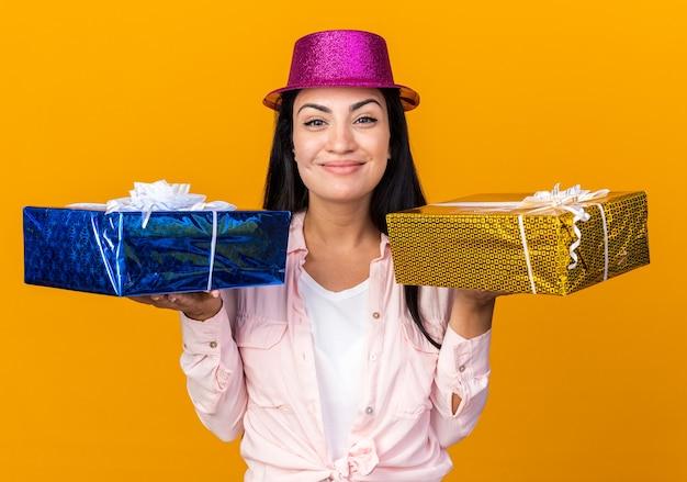 Blij jong mooi meisje met feestmuts met geschenkdozen geïsoleerd op een oranje muur