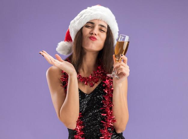 Blij jong mooi meisje met kerstmuts met slinger op nek met glas champagne weergegeven: kus gebaar geïsoleerd op paarse achtergrond