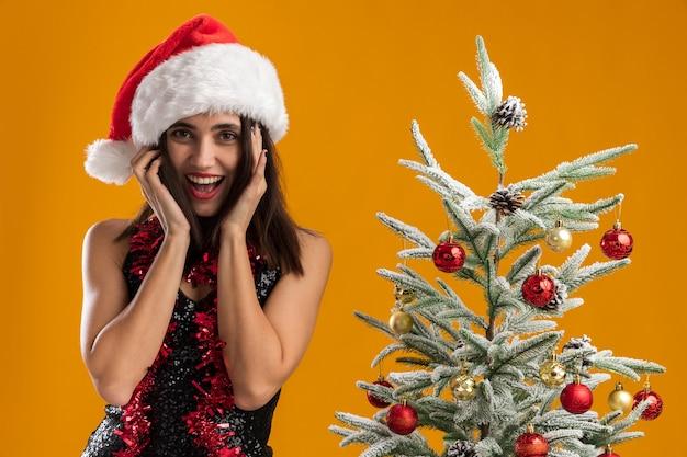 Blij jong mooi meisje met kerstmuts met slinger op nek staande in de buurt van kerstboom geïsoleerd op een oranje achtergrond