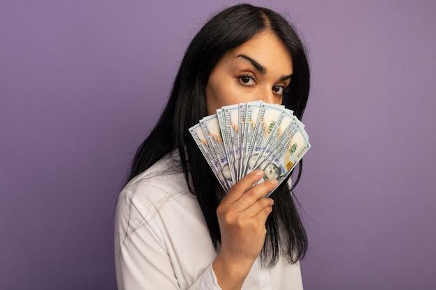 Blij jong mooi meisje met wit t-shirt bedekt gezicht met contant geld geïsoleerd op paars