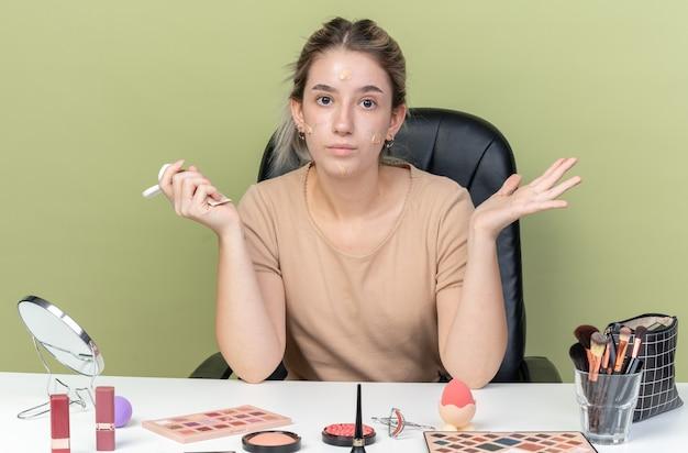 Blij jong mooi meisje zit aan bureau met make-up tools met tone-up crème op gezicht met toon crème verspreiden hand geïsoleerd op olijf groene muur