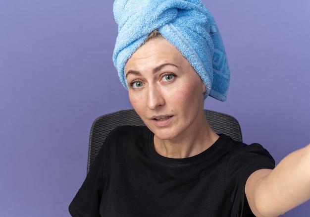 Blij jong mooi meisje zit aan tafel met make-uptools die haar afvegen in een handdoek met camera geïsoleerd op blauwe muur