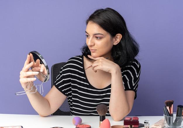 Blij jong mooi meisje zit aan tafel met make-uptools met make-upborstel en kijkt naar spiegel in haar hand geïsoleerd op blauwe muur