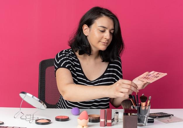 Blij jong mooi meisje zit aan tafel met make-uptools met oogschaduwpalet met make-upborstel geïsoleerd op roze muur
