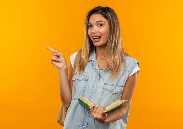 Blij jong mooi studentenmeisje die achterzak dragen die open boek houdt en naar kant wijst die op oranje wordt geïsoleerd